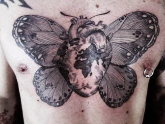 An Otto D Ambra tattoo that combines a human heart, planet earth and a butterfly