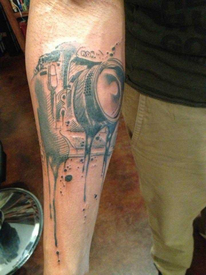 An illustration of a camera melts in this tattoo design by Pietro Romano