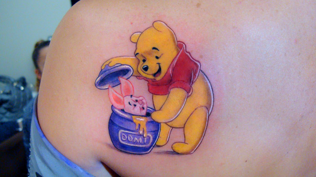 An incredible tattoo of Winnie the Pooh discovering Piglet in a honey jar