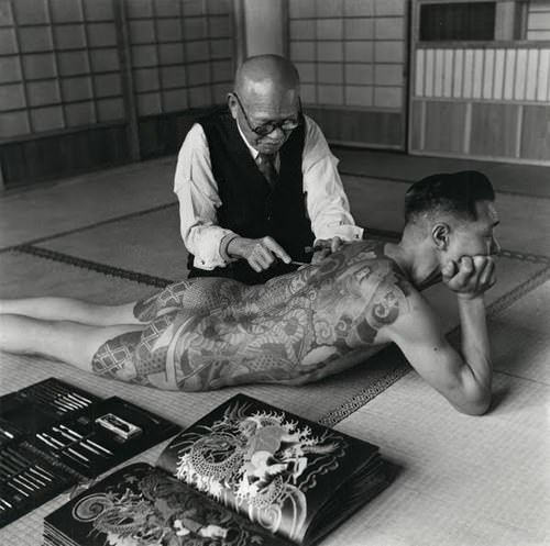 An irezumi artist tattoos a yakuza member with the traiditional hand poking method