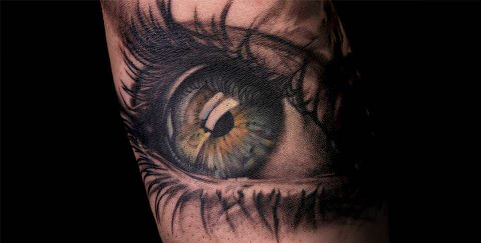 Niki Norberg combines greyscale and color areas to add appeal to this realistic eye tattoo