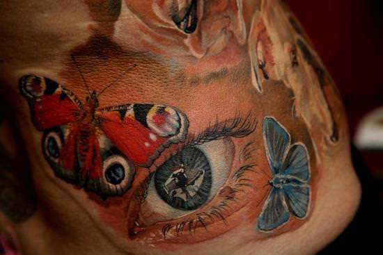 This feminine tattoo of a realistic eye surrounded by butterflies is a combination of symbols