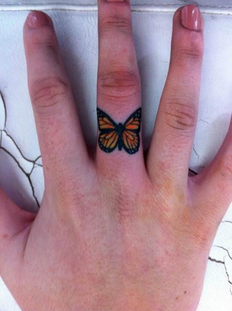 A cute butterfly tattoo on the finger that acts as permanent jewelry