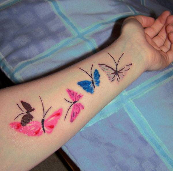 A scattering of painted butterflies makes for a fun, artistic tattoo design