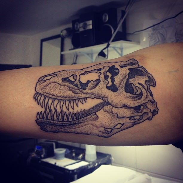 A dot work tattoo of a dinosaur skull by Gregorio Marangoni