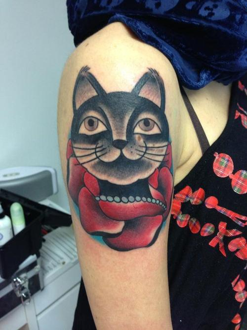 A happy cat with a rose makes up this tattoo design in an American traditional style