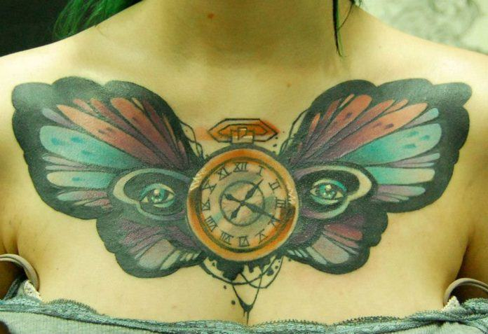 A pocket watch and human eyes add symbolism to this butterfly chest tattoo by Jukan