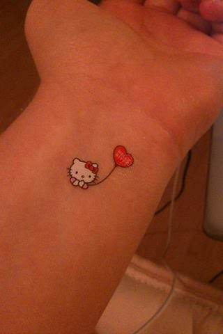 A tiny Hello Kitty tattoo on the wris looks almost like a sticker