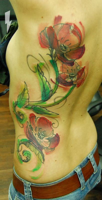 Berlin tattoo artist Jukan creates a beautiful watercolor tattoo of poppy flowers