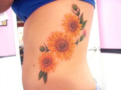 Sunflowers and thistles make up this bright and colorful flower tattoo design