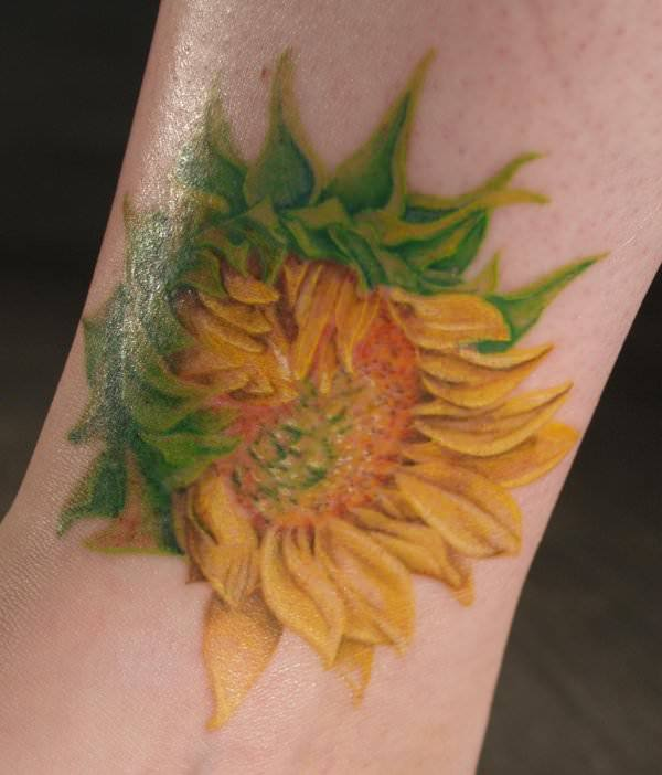 This artistic sunflower tattoo shows how the petals of the flower unravel from the heart outwards