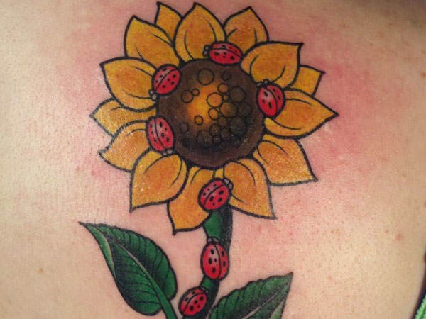 This cute sunflower and ladybug tattoo design is in the style of a childrens book illustration
