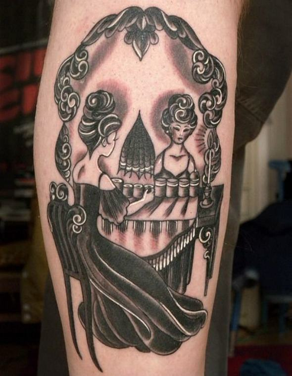 This optical illusion tattoo shows either a woman in front of a dressing table or a human skull