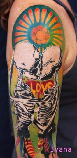 Two skeletons kiss in front of the word LOVE in this artistic tattoo by Ivana Belakova