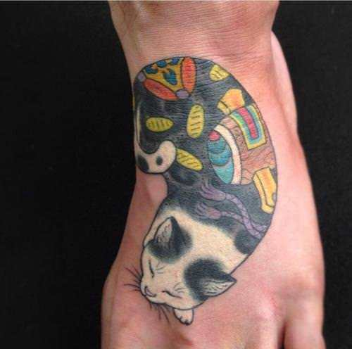 White tattoo ink really makes this tattoo of a cat sleeping stand out from the skin