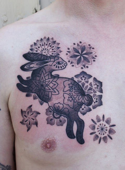 Spanish tattoo artist Gemma Pariente combines dotwork textures and gradients in this bunny rabbit and flowers tattoo