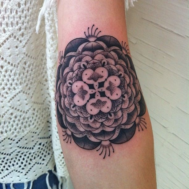 This feminine mandala flower tattoo by Gemma Pariente boasts her signature dot work and gradient textures