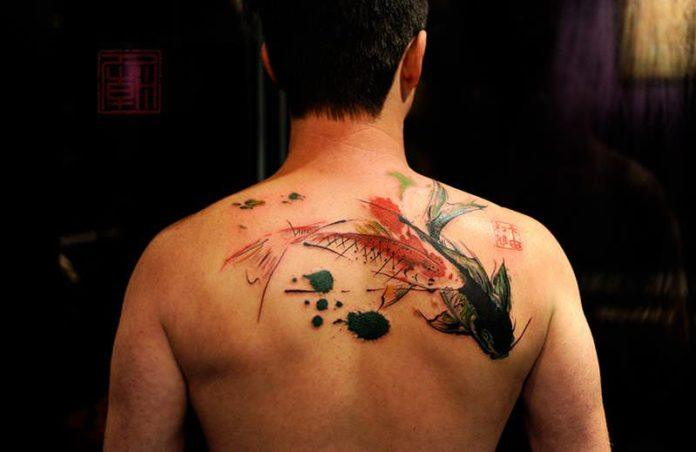 Two koi fish get a modern design style in this artistic abstract tattoo from Tattoo Temple studio in Hong Kong
