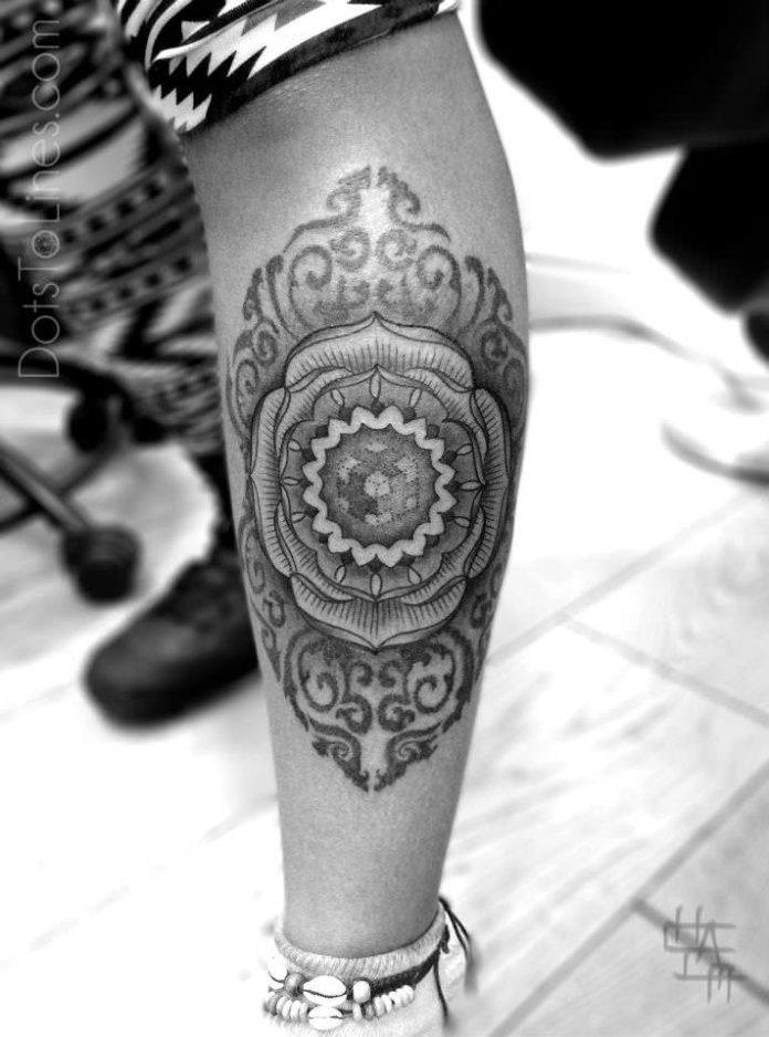 Amazing sacred geometry tattoo by Chaim Machlev of a mandala flower with a dotwork cube