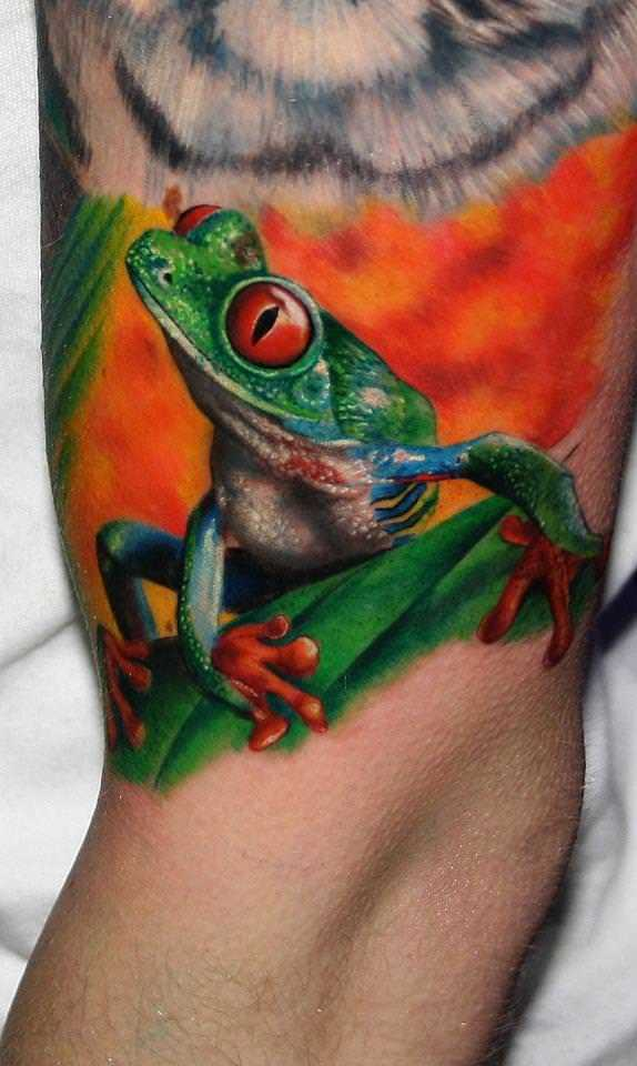 This bright, cute and colorful tree frog tattoo by Carlox Angarita is a bold statement for nature lovers