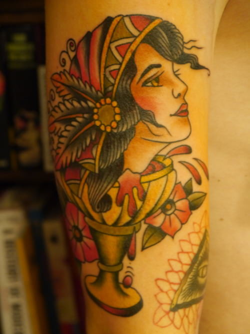 A beautiful woman is trapped in a wine goblet in this modern takes on the American Traditional tattoo style by Karl Wiman