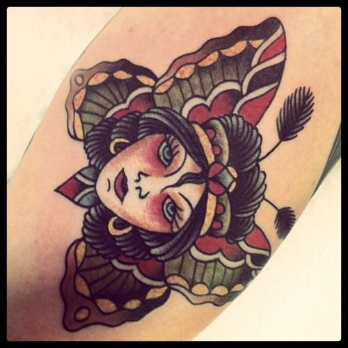 A beautiful woman surrounded by butterfly wings captivates the viewer in this old school tattoo by Karl Wiman
