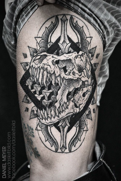 A dinosaur skull roars out from the center of a mandala design in this black ink tattoo design by Daniel Meyer