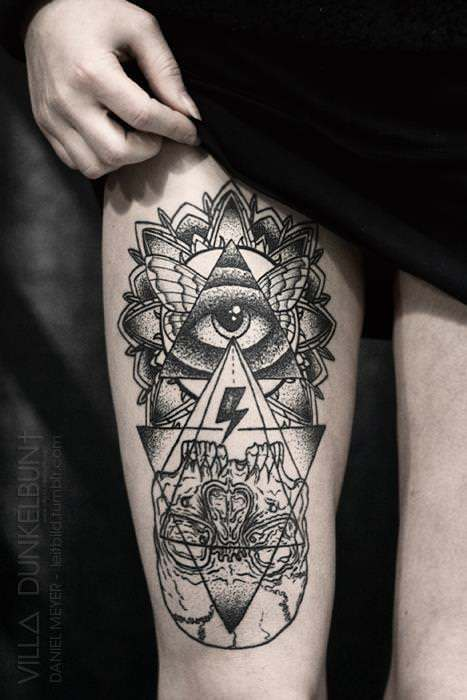 A human eye in a triangle with butterfly wings and a mandala flower visualizes an upside down skull in this tattoo by Daniel Meyer