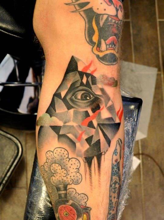 A human eye peers out from between cubist shapes in this artistic tattoo by Marcin Surowiec