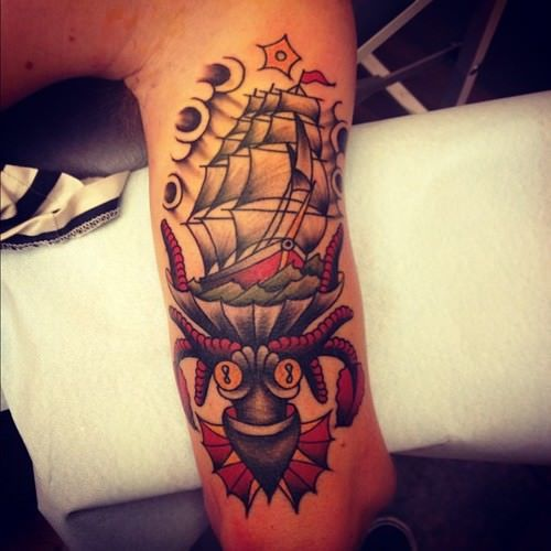 A monster octopus eats a ship at sea in this modern take of the American Traditional tattoo style by Karl Wiman