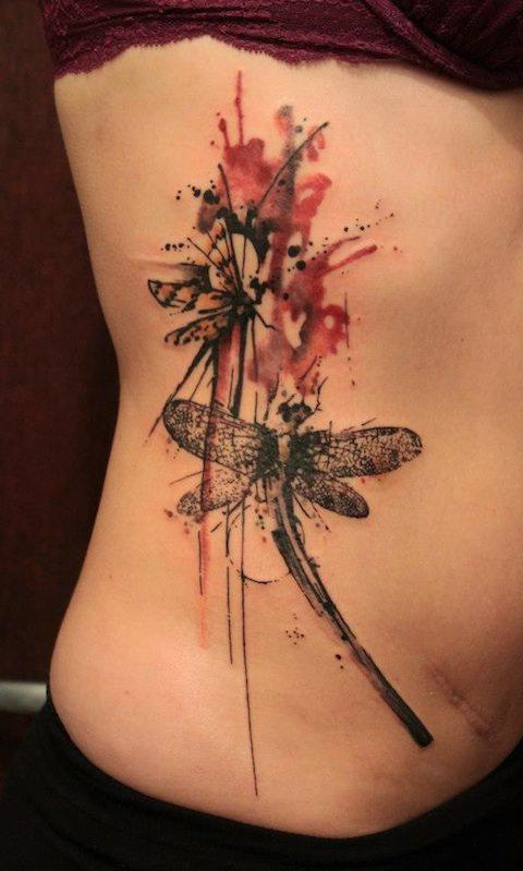 Abstract dragonflies flutter together in this splashy watercolor tattoo by Gene Coffey