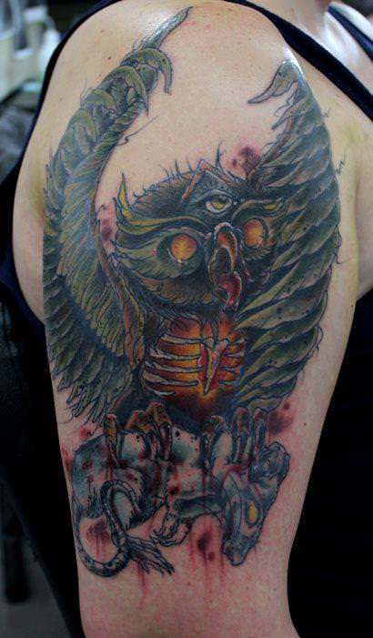 An owl with three eyes clutches a rat in this artistic watercolor tattoo by Australian artist Mel Wink