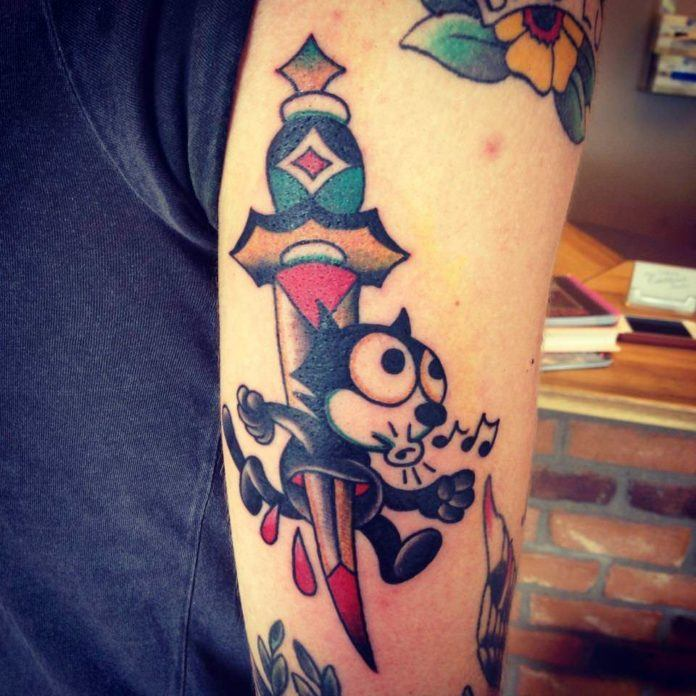 Felix the Cat is stabbed through by a dagger in this modern take on the American Traditional tattoo style by Karl Wiman