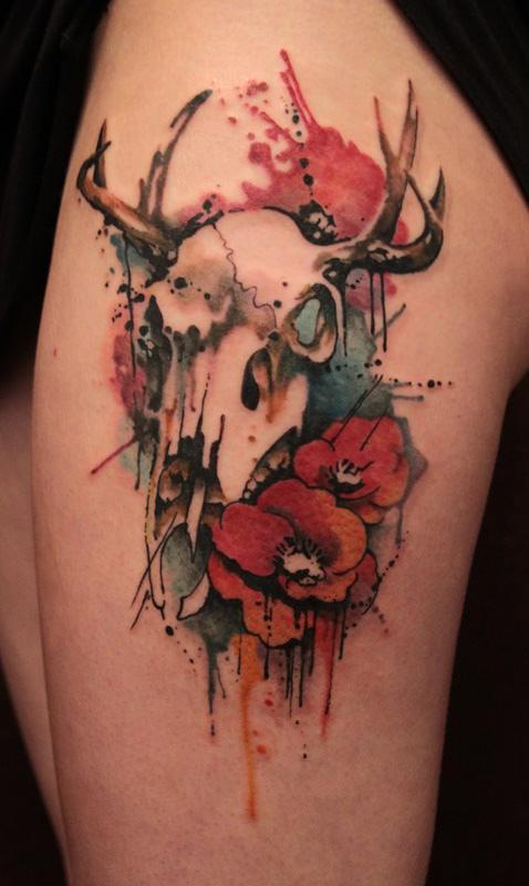 Gene Coffey tattoos symbols of life and death in this artistic watercolor tattoo of an animal skull and poppy flowers