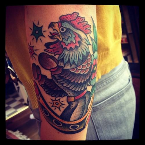 Tattoo artist Karl Wiman makes this fighting rooster into a boxer in this unusual tattoo in the American Traditional style