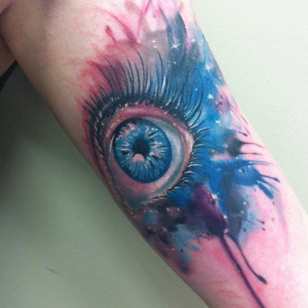 Tattoo artist Mel Wink combines realism and watercolor painting in this artistic tattoo of a womans eye