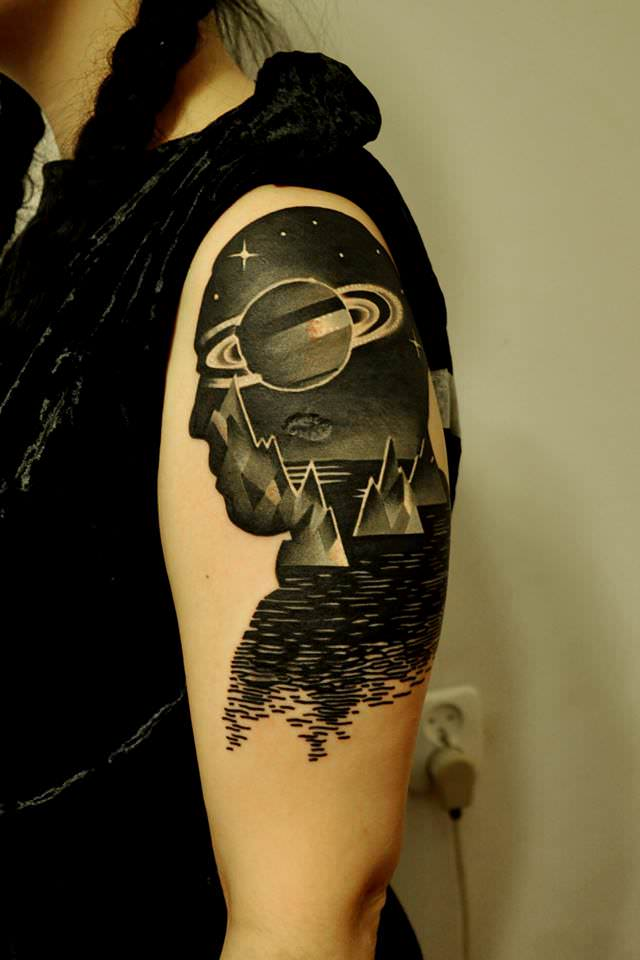 This tattoo by Marcin Surowiec boasts a surrealist scene with cubist icebergs inside the silhouette of a man