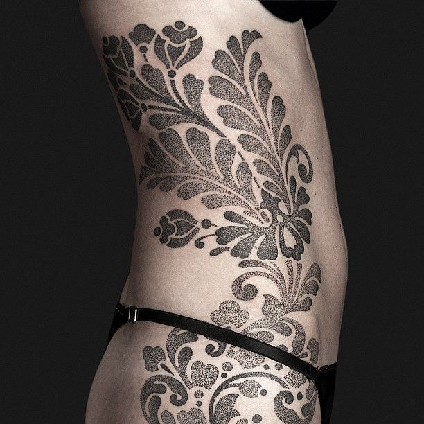 Infinitely feminine, this textural floral tattoo by Nazareno Tubaro flows with the shape of this woman body