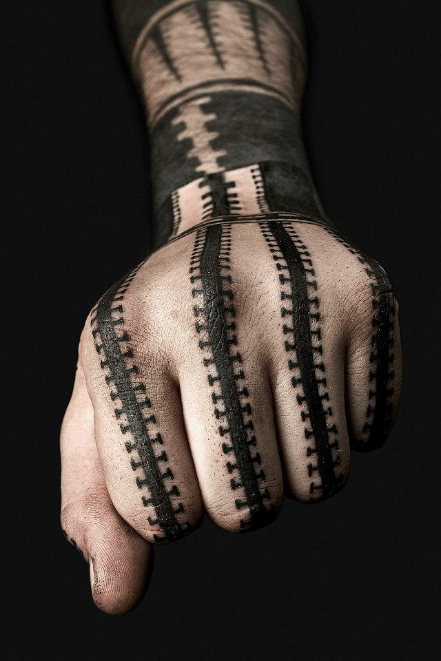 This unusual but appealing geometry tattoo by Nazareno Tubaro uses a repetitive pattern that fits the shape of the hand