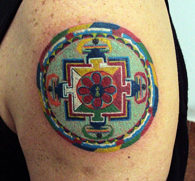 The spiritual significance of this sacred geometry mandala tattoo lies in its use of traditional colors and shapes