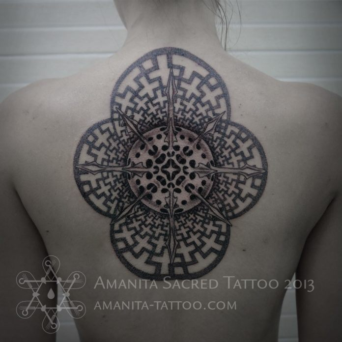This stunning back tattoo by Mike Amanita uses geometric and organic shapes to create an insterstellar feeling