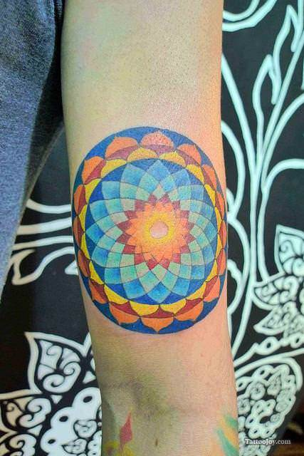 Using mostly primary colors, this flower of life mandala tattoo is friendly and fun.