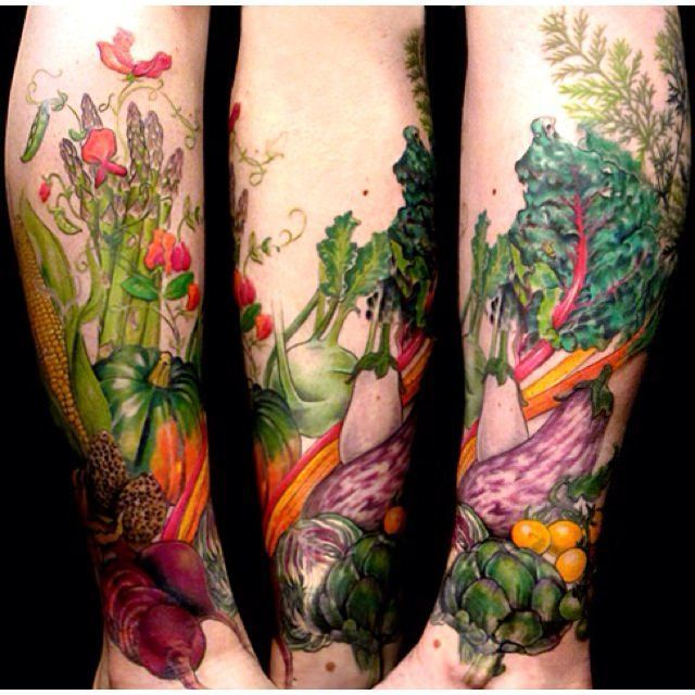 This tattoo by Butterfat studios features a bounty of fresh vegetables as a symbol of fertility and femininity