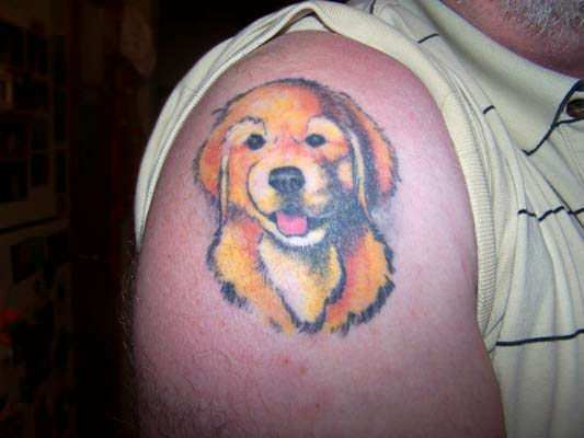 A golden retriever puppy grins out of this cute tattoo celebrating a favorite pet