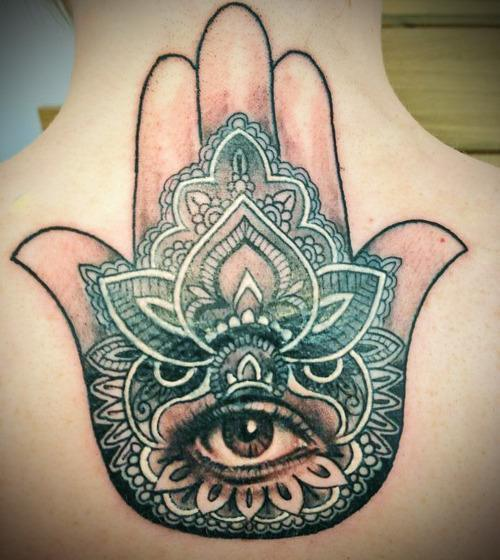 A realistic eye stares out from the palm of this religious hamsa hand tattoo decorated with mandala designs