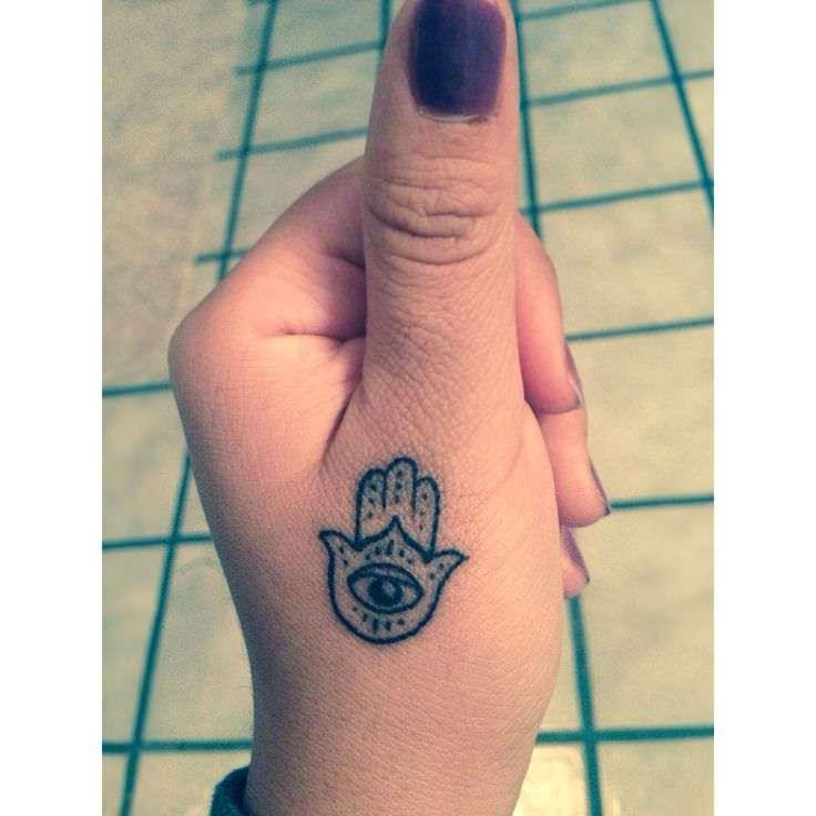 a tiny hamsa tattoo below the thumb ensures that its