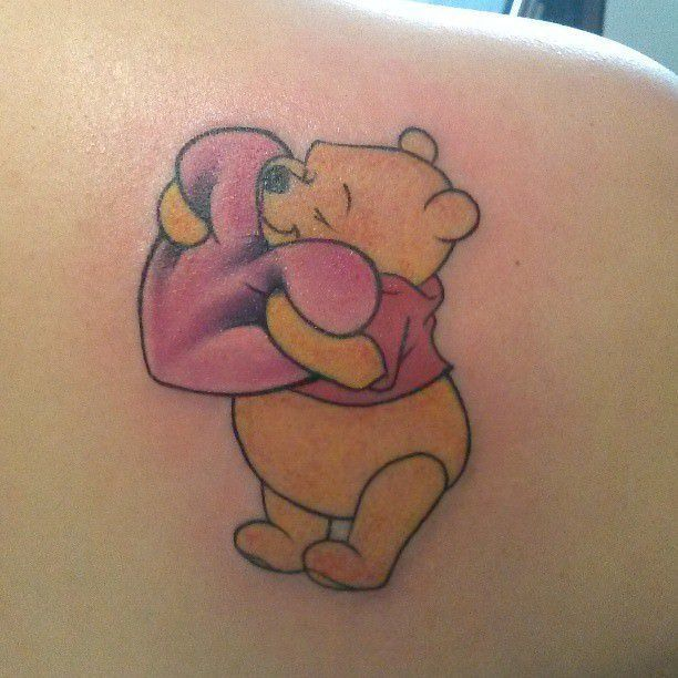 Cuddly and courageous, the friendly Pooh Bear hugs a heart in this cute and lovable tattoo design