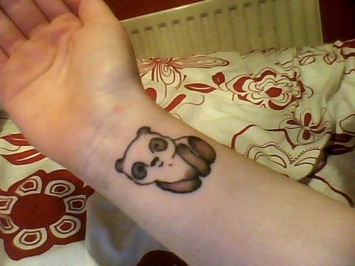 Simply adorable! A cute little panda looks out of this wrist tattoo design