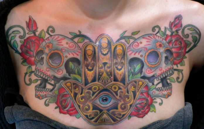 This Hamsa hand tattoo has a distinct Mexican flavor with its sugar skulls and roses