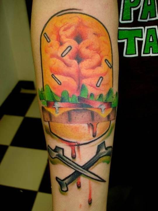 A brain burger is the skull in this skull and crossbone tattoo by Mark Halbstark
